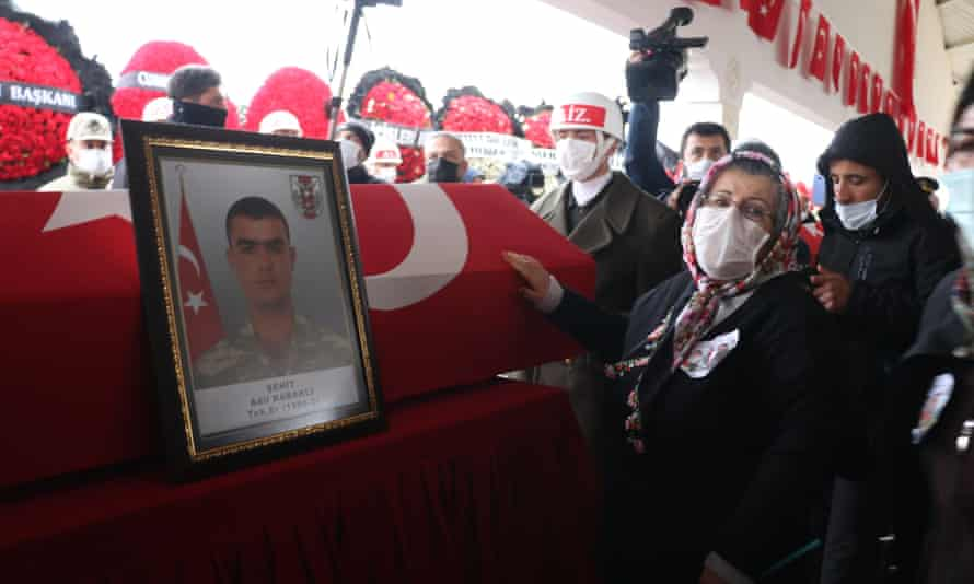 The grandmother of a Turkish soldier, Adil Kabakli, touches his coffin during his funeral