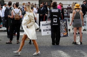 A show-goer walks past Extinction Rebellion protesters as they demonstrate against London fashion week.