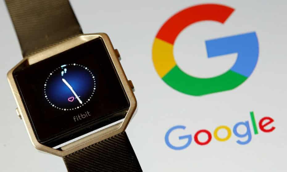 A Fitbit smartwatch beside a Google logo