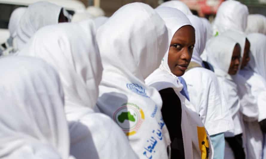 Girls in headscarves wait in line.