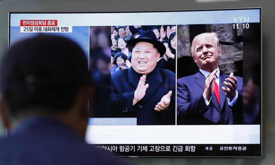 A man watches a TV screen showing file footage of U.S. President Donald Trump, right, and North Korean leader Kim Jong Un