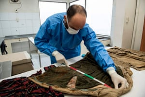 Stefano Di Lucca of Chile's legal medical service measures an item of recovered clothing