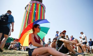 A woman sits under an umbrella as temperatures rise to 30C.