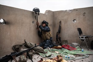 An Iraqi federal policeman uses a helmet on a stick to try and draw fire from an Islamic State sniper in an attempt to make him reveal his position during the battle to recapture western Mosul.