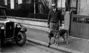 An alsatian guide dog stops his blind owner from stepping off a pavement into the path of a car. The 'owner' Captain Liakhoff is a trainer for the British Guide Dogs for the Blind at Wallasey, Cheshire, April 1934.