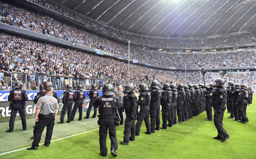 Police secure the pitch after trouble broke out during the game.