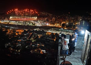 People watch fireworks exploding over the Maracanã, from a terrace in the Mangueira favela, during the opening ceremony.