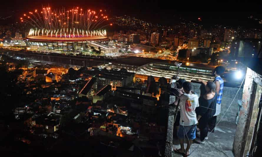 Residents of the Mangueira favela watch the fireworks at the Maracanã stadium during the Olympic opening ceremony.