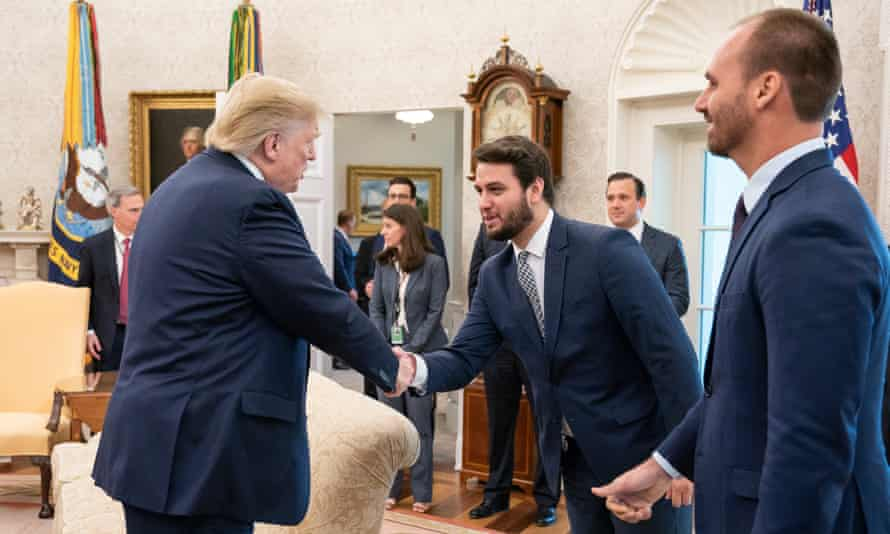 Filipe Martins, Jair Bolsonaro's foreign policy adviser, shakes hands with Donald Trump in the Oval Office in Washington.