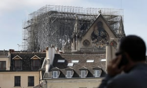 A man speaks on a mobile phone as he looks at the Notre Dame Cathedral, in Paris, Wednesday, April 17, 2019. Nearly $1 billion has already poured in from ordinary worshippers and high-powered magnates around the world to restore Notre Dame Cathedral in Paris after a massive fire. (AP Photo/Christophe Ena)