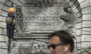 A man walks past the Pacific Gas & Electric building in San Francisco.