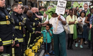 Friends and relatives meet firefighters during the silent walk on the Grenfell Tower anniversary in June this year.