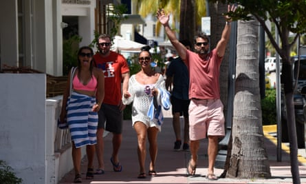 Groups of people are seen not wearing masks in Miami Beach. Florida's death toll from coronavirus has hit 10,000.