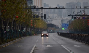 A lone car drives down a disserted street in Wuhan on Sunday.