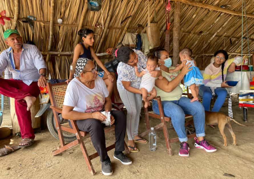 Yirley Velasco, seated with baby, visits families in a rural area of Montes de Maria