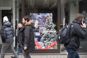 Pedestrians pass a shop on Regent Street displaying Christmas decorations