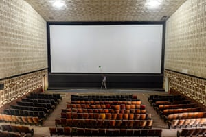 A worker cleans the screen in a cinema hall in Chennai, India
