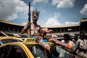 Kinshasa, CongoA Congolese wrestler's fetisheur sits on top of a car as he arrives to the Stade De Martyrs for a sports exhibition day