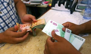 Currency is changed at a currency exchange in the Souk il-Jumaa district in Tripoli.