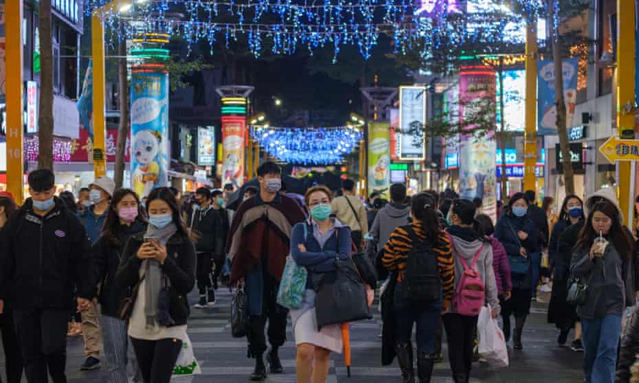 People wear face masks as they pass shops in Ximen, Taipei, Taiwan.