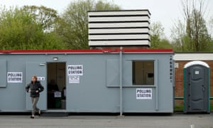 A woman leaves a polling station as voting begins in local government elections in Manchester
