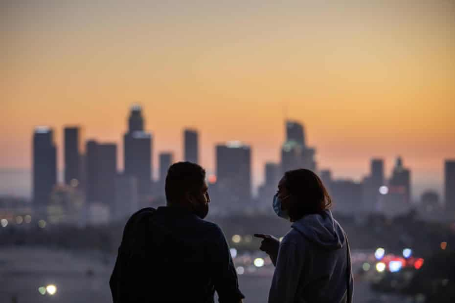 A couple wearing facemasks to prevent the spread of coronavirus watch the sunset from Elysian Park in Los Angeles, California, on November 14, 2020.