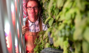 Jens Thomas stands between the rows of optimised LED lighting and vertical strips of vegetables growing on moveable racks.