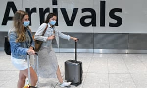 Passengers wearing face coverings arrive at Heathrow airport, west London, on 10 July 2020