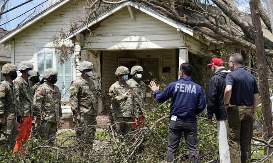 Donald Trump and the acting homeland security secretary, Chad Wolf, speak with national guard soldiers helping clean up after Hurricane Laura, in Lake Charles, Louisiana.