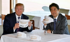 Donald Trump and Shinzo Abe pose with their customised white baseball caps,