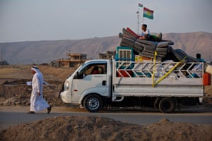 A young boy sits on top of a truck containing his families belongings as they make the slow journey on the road back to Mosul, Iraq