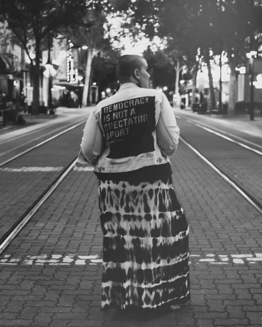 A woman dons a jacket saying 'Democracy is not a spectator sport' on city street in Sacramento, Calif.