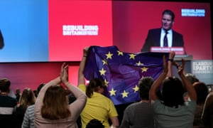 Conference attendees hold up an EU flag during  shadow Brexit secretary's speech
