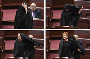 One Nation leader Pauline Hanson takes off a burqa she wore wore to question time in the Senate chamber.