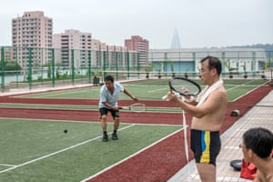 Men play tennis and relax at the Munsu Water Park complex.