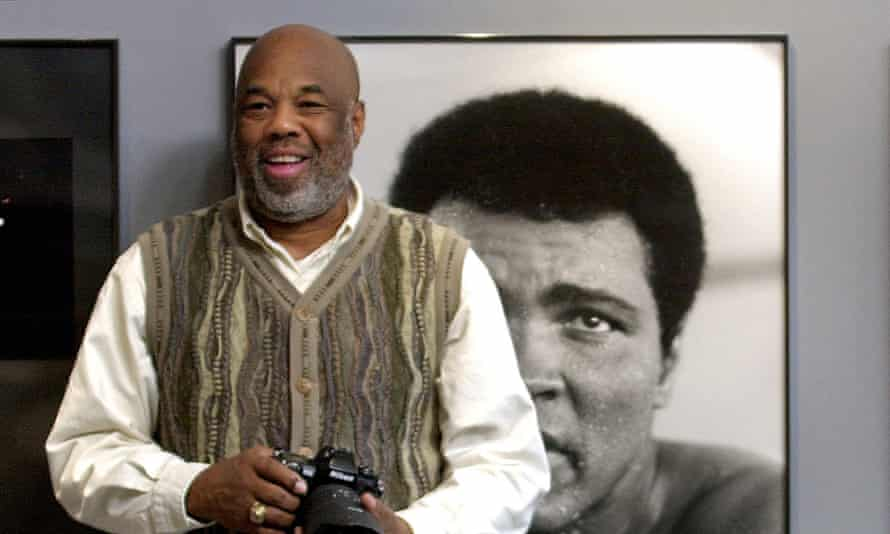 Howard Bingham stands next to photos of Muhammad Ali, part of an exhibit of his works in 2002 at the Smithsonian in Washington