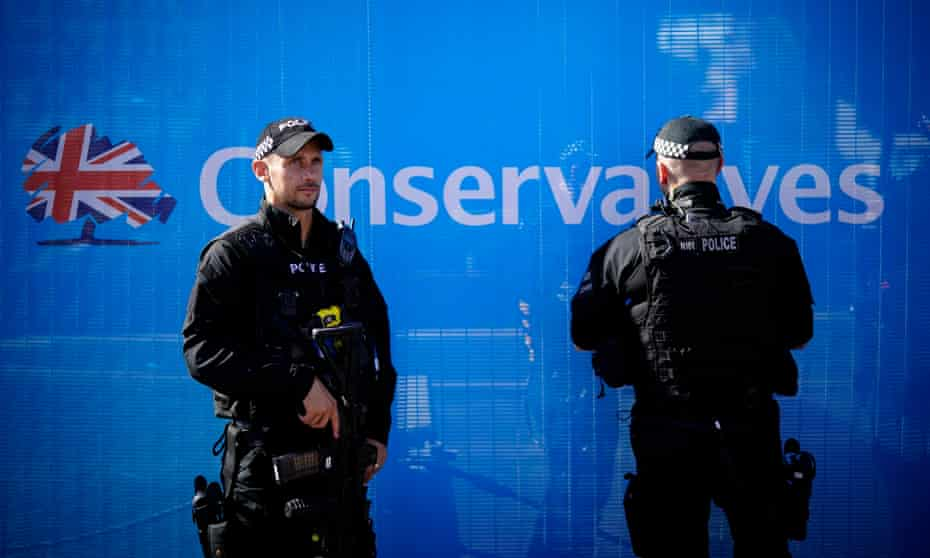 Armed police officers patrol and keep watch as politicians and delegates begin to arrive for the annual Conservative party conference.