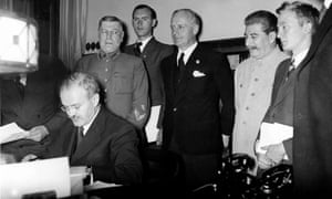 Vyacheslav Molotov (left) signs the pact as Joachim von Ribbentrop (centre) and Joseph Stalin watch