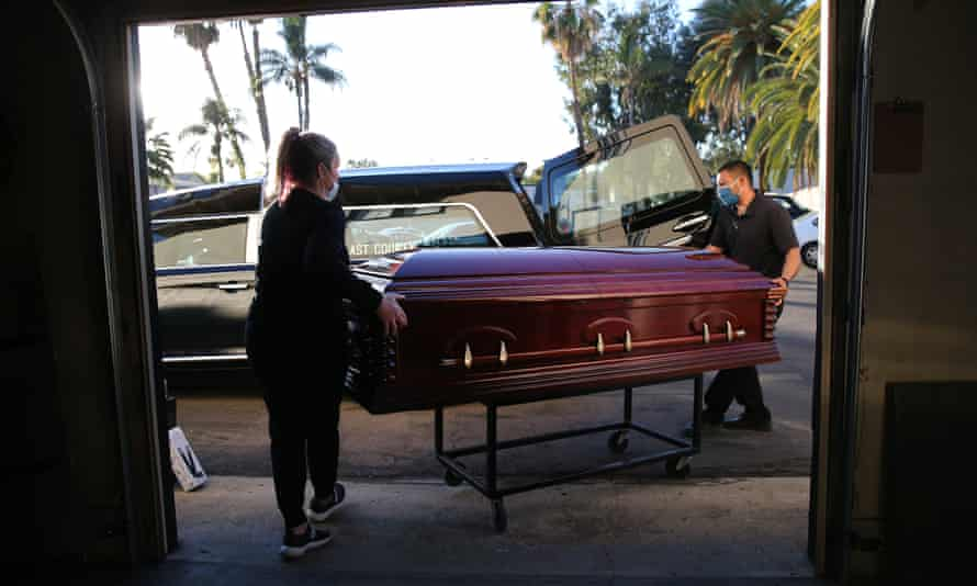 Funeral workers load the casket of a person who died after contracting Covid-19 into a hearse at East County Mortuary in El Cajon, California.