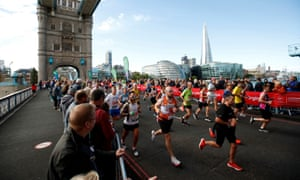 Spectators watch runners during the London Marathon as they run over Tower Bridge.