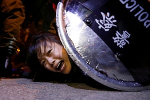 An anti-extradition bill protester is detained by riot police during a protest outside Mong Kok police station.
