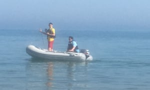 A couple of officials in a dinghy warn people to get out of the water.