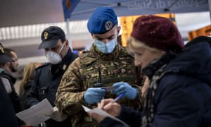 People wearing face masks are checked for coronavirus at the Termini Central in Rome.