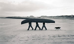 three men carrying an upturned boat across a beach