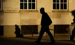 Silhouette of a man walking on an anonymous street.