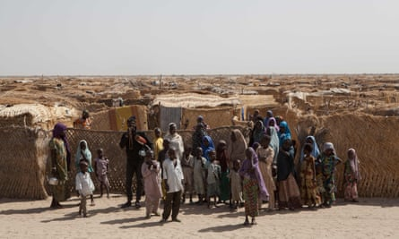 Displaced families stand at the main gate of a camp for internally displaced people at Monguno, Borno state