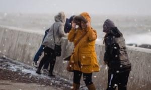 People walk through flying sea foam spray in Porthcawl.