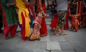 A girl in traditional attire walks with her mother during a ceremony in Kathmandu