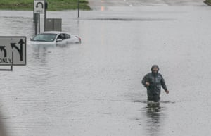 A man walks through the flooded feeder roads off of Highway 69 North on 19 September 2019 in Houston, Texas.