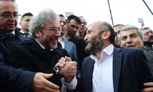 Can Dündar (left) and Erdem Gül hold hands as they arrive at the Istanbul courthouse before the trial.